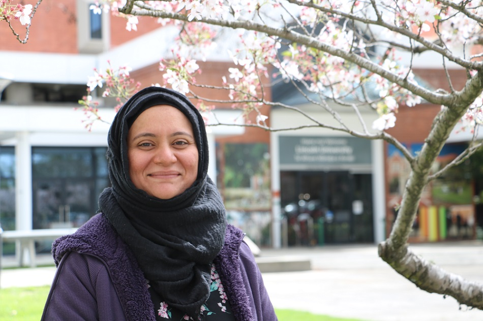 A woman in a hijab smiling in front of a cherry tree