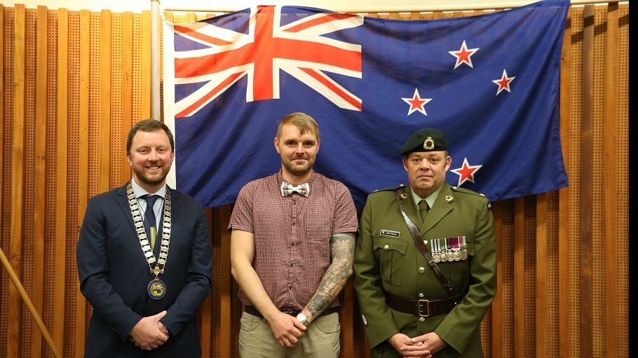 Picture of Mayor Sam Broughton, blonde man in red check shirt and bow-tie and New Zealand Army Major in uniform in front of a New Zealand flag