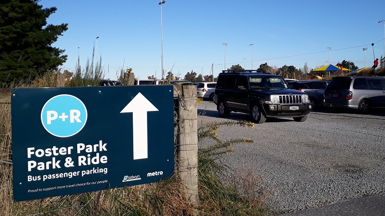 Picture of a blue sign on a fence saying park and ride, with cars parked in the background and black car driving out the gate