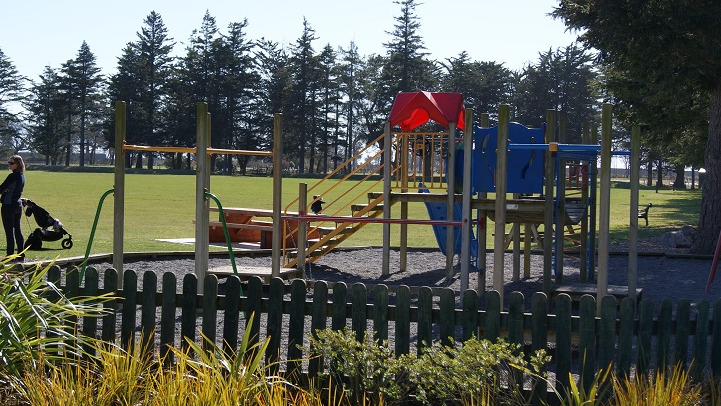 A picture of the Kirwee Domain playground with two women in the distance and a sports field behind