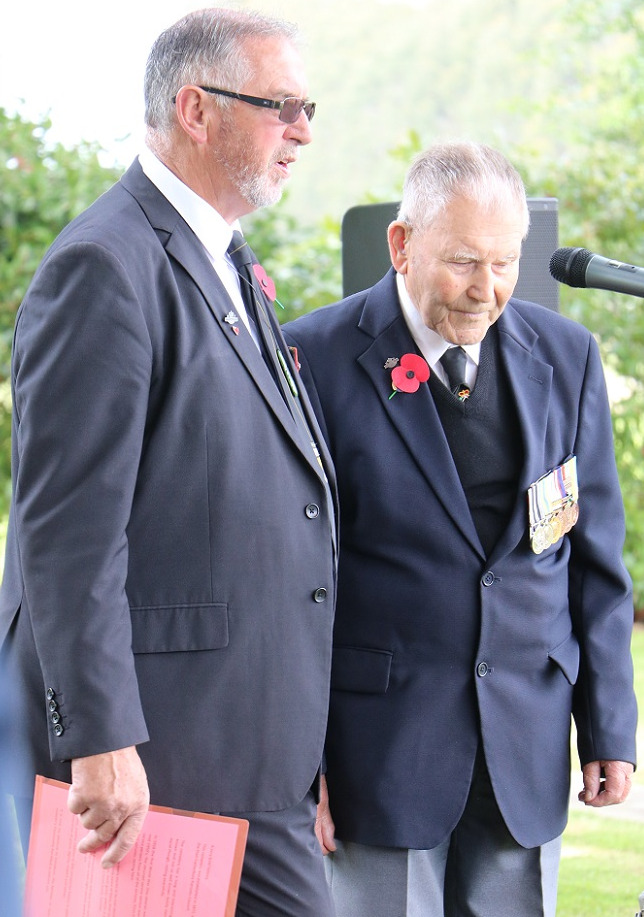 A grey haired man in a blue suit stands next to an elderly man in a suit wearing a poppy and a row of medals
