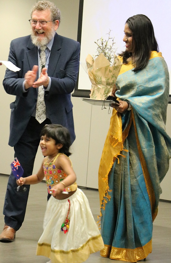 A woman in a sari, carrying a plant and Deputy Mayor Malcolm Lyall laugh as a young girl in a sari runs away smiling carrying a small New Zealand flag