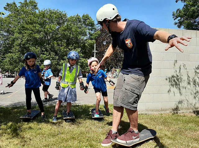 A man balances on a skateboard with his arms out wide, looking behind and talking to three primary school girls in uniform and helmets standing on skateboards