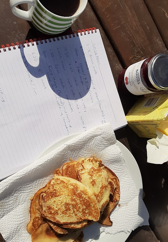 Close up of a coffee cup, hand written recipe in notebook, pikelets, jam and butter