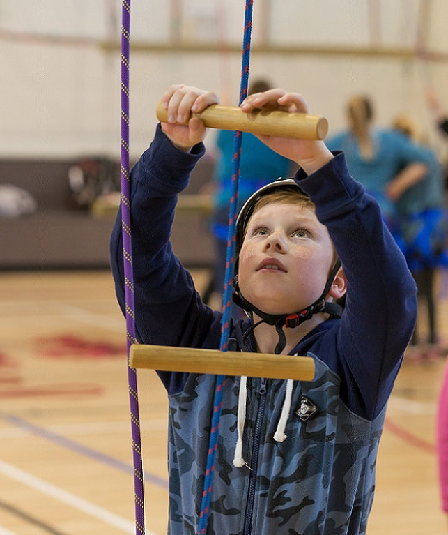 Boy in blue camouflage jersey and white climbing helmet gets ready to climb a rope ladder
