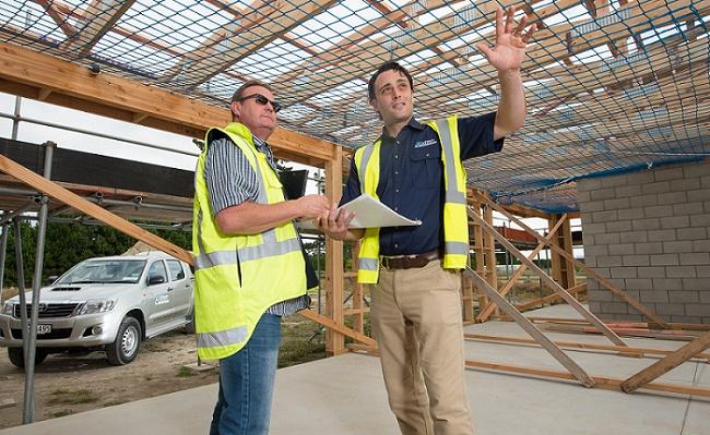 Two men in hi-viz jackets talk inside a half-built building, one pointing