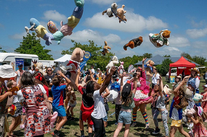 A crowd of children throwing teddy bears in the air