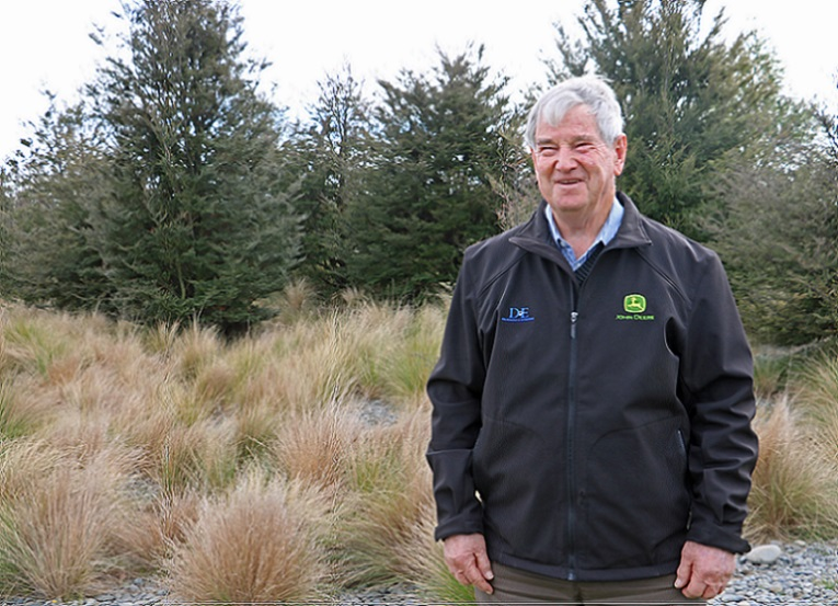 An elderly man with grey hair wearing a black windbreaker with a John Deere logo on it stands laughing in front of some small pine trees and tussock grass