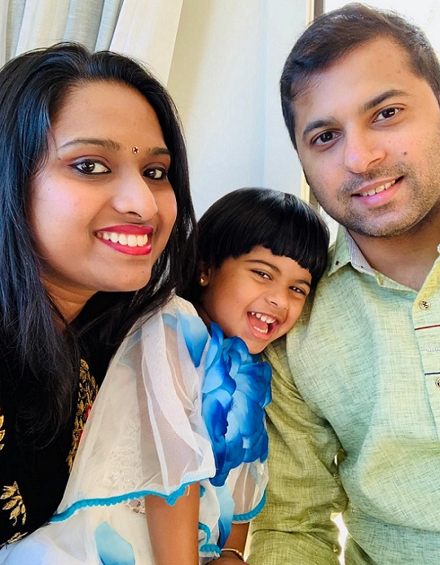 A smiling mum and dad sit leaning in close on either side of a laughing girl in a blue and white dress