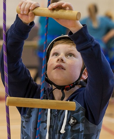 Boy in blue camouflage jersey and white climbing helmet gets ready to climb a rope latter