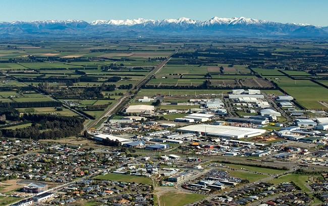 An aerial view of Rolleston looking over houses, I-zone and out to the Southern Alps