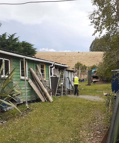 A man in yellow high vis jacket conducting a welfare check on a house