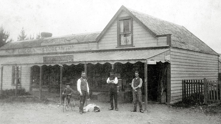 A faded black and white photograph of a child on a bicycle and three men in suits standing in front of a wooden building labeled Lincoln Store. A large white dog with a brown haired head lies on the ground at one of the men's feet