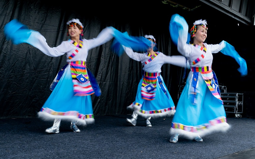 Three dancers in traditional outfits of blue with extra long sleeves, multi coloured checker trim and silver boots dance at CultureFest