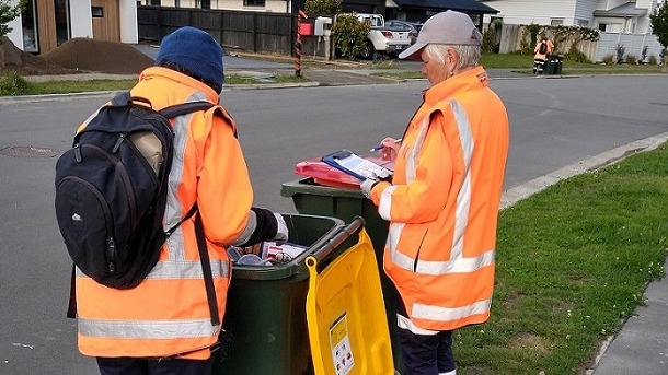 Two people checking recycling bin
