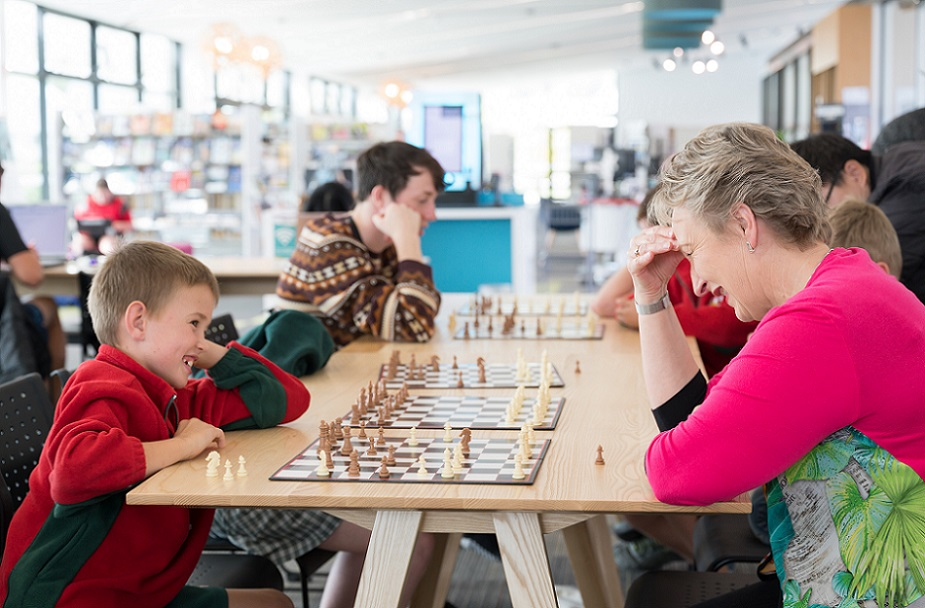 A child and an woman play chess in the foreground of a row of others playing chess